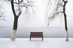 Lonely winter bench beside West Lake, Hangzhou. HANGZHOU, CHINA - JAN 4, 2013 - Lonely winter bench beside West Lake, Hangzhou royalty free stock photos