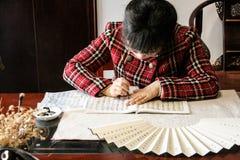 Hangzou, Chiny - May 22, 2016: Mrs Mai pisze puszkowi chińskich symbolach na ręcznie robiony fan Fotografia Stock