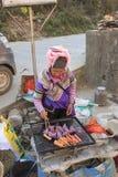 Hani kvinna som förbereder gatamat i Shengcun den lokala marknaden i YuanYang Hani är en av de 56 minoriteterna i Kina och är nat Royaltyfria Bilder