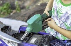 Hanjongen die brandstof opvullen in de motor stock afbeeldingen