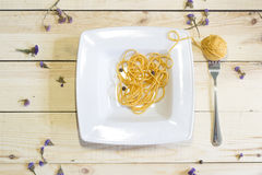 Hank on a fork like spaghetti in the plate on a wooden background Royalty Free Stock Image