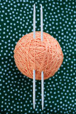 Hank orange thread and two needles on a background Royalty Free Stock Photography