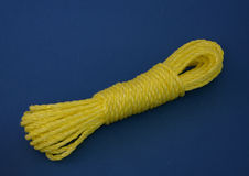 Hank of yellow  plastic linen rope over blue Royalty Free Stock Image