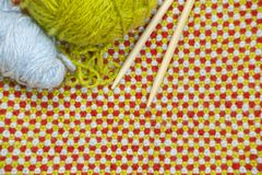 Hanks of red, green yarn and knitting needles on the background of knitted, woolen cloth Stock Photo