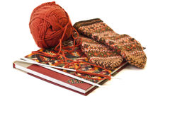 Hanks of wool, knitting needle, book and a mitten. Royalty Free Stock Images