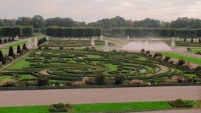 Hannover, Alemanha Testes padr?es bonitos dos arbustos e das hortali?as no jardim Uma grande fonte de espirrar a ?gua no filme