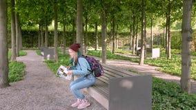 Hannover, Alemanha Um turista fêmea novo com um mapa em suas mãos e em uma trouxa senta-se em um banco de pedra no parque vídeos de arquivo