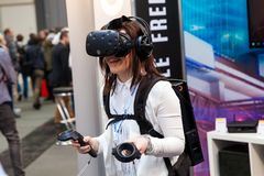Girl playing video game in virtual reality headset and handheld controllers developed by HTC Vive on exhibition Cebit. Hannover, Germany - March, 2017: Girl Stock Photography
