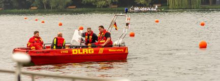 A red boat of the German company for the rescue of lives with three persons drives over the Maschsee stock photography