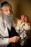 Hannukah candles. Old jewish man lighting candles of a hannukah menorah Stock Photography
