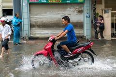 Hanoï, Vietnam - 17 juillet 2017 : Un motocycliste monte le long de la rue inondée de Minh Khai dans la ville de Hanoï, Vietnam Photos stock