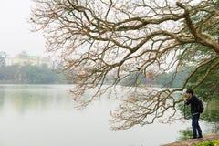 Hanoï, Vietnam - 15 mars 2015 : Le jeune homme prend la photo du bourgeon d'arbre au lac Hoan Kiem dans la capitale de Hanoï avec Photographie stock libre de droits