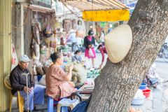 Hanoi street life. In Vietnam behind a traditional hat on a tree Stock Image