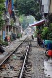 Hanoi train street, Vietnam. Train tracks running between homes in Hanoi, Vietnam, with rubbish, people and trees Stock Photos