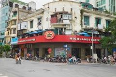 Hanoi, Vietnam - 30 agosto 2015: Vista esteriore anteriore del caffè degli altopiani sulla via di Le Duan, con i veicoli che tras Immagine Stock