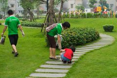 Hanoi, Vietnam - Apr 19, 2015: Family volunteers picking up litter in the park at Times City, a luxury and high class combination. Of apartment and mega mall Stock Photography