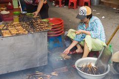 Hanoi, Vietnam - Apr 5, 2015: A woman broil barbecue meat - the ingredient of Bun Cha is the famous Vietnamese noodle soup with bb. Q meat, spring roll Royalty Free Stock Images