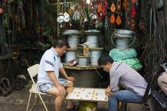 Hanoi, Vietnam - 20 April, 2014: De niet geïdentificeerde mensen spelen schaak voor een het bewerken opslag op de straat van Hano Stock Foto
