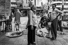 Hanoi, Vietnam - April 13, 2018: De vrouwelijke straatventer loopt onderaan de straten van Hanoi Stock Foto