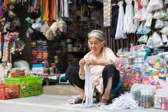 Hanoi Vietnam - April 5, 2015: Gammal vietnamesisk kvinna som arbetar i ett lager för klädtillbehör i den Hang Bo gatan, Hanoi Royaltyfria Bilder