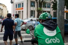 Hanoi, Vietnam - April 15, 2018: Grab driver waits for Clients on the streets of Hanoi. Hanoi, Vietnam - April 15, 2018: Grab driver waits for Clients on the royalty free stock photography
