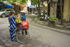 Hanoi, Vietnam - April 13, 2014: Unidentified food vendor sells fruits carried by bike to a woman on Hanoi street, Vietnam.  Royalty Free Stock Photos