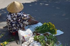 Hanoi, Vietnam, April 3, 2019: A vietnamese woman seated on the road sells flowers stock photos