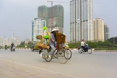 Hanoi, Vietnam - 13 aprile 2014: Traffichi sulla via di Hanoi con le costruzioni in costruzione su fondo La regione capitale di H Fotografia Stock