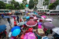 Hanoi, Vietnam - 24 Augustus, 2017: Bezige straat met overvolle mensen die paraplu in regenachtige ochtend op een straat in Tijde Stock Foto's