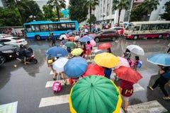 Hanoi, Vietnam - 24 Augustus, 2017: Bezige straat met overvolle mensen die paraplu in regenachtige ochtend op een straat in Tijde Royalty-vrije Stock Fotografie