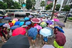 Hanoi, Vietnam - 24 Augustus, 2017: Bezige straat met overvolle mensen die paraplu in regenachtige ochtend op een straat in Tijde Royalty-vrije Stock Foto's