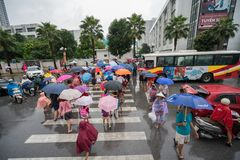 Hanoi, Vietnam - 24 Augustus, 2017: Bezige straat met overvolle mensen die paraplu in regenachtige ochtend op een straat in Tijde Stock Fotografie