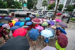 Hanoi, Vietnam - 24 Augustus, 2017: Bezige straat met overvolle mensen die paraplu in regenachtige ochtend op een straat in Tijde Royalty-vrije Stock Foto