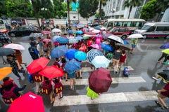 Hanoi, Vietnam - 24 Augustus, 2017: Bezige straat met overvolle mensen die paraplu in regenachtige ochtend op een straat in Tijde Stock Foto