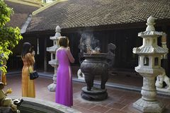 Hanoi, Vietnam - 23 Augustus, 2015: Boeddhisten die in Vietnamese traditionele kleding Ao Dai bij Tran Quoc-tempel bidden Tran Qu Stock Afbeelding