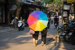 Hanoi, Vietnam - 24 de abril de 2016: Paraguas colorido de dos muchachas en la calle de Hang Vai Con el tiempo típico del tipo tr Fotos de archivo