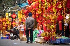 Hanoi, Vietnam - 26 de enero de 2017: El viejo hombre toma una decoración y una flor de compra del paseo por Año Nuevo lunar viet Imagenes de archivo