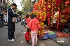 Hanoi, Vietnam - 26 de enero de 2017: La gente toma una decoración y una flor de compra del paseo por Año Nuevo lunar vietnamita  Foto de archivo