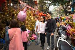 Hanoi, Vietnam - 26 de enero de 2017: La gente toma una decoración y una flor de compra del paseo por Año Nuevo lunar vietnamita  Imagen de archivo libre de regalías