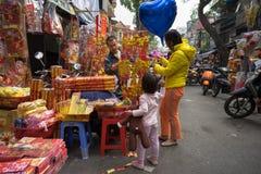 Hanoi, Vietnam - 26 de enero de 2017: La gente toma una decoración y una flor de compra del paseo por Año Nuevo lunar vietnamita  Fotografía de archivo libre de regalías