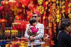 Hanoi, Vietnam - 26 de enero de 2017: La gente toma una decoración y una flor de compra del paseo por Año Nuevo lunar vietnamita  Fotos de archivo libres de regalías