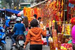 Hanoi, Vietnam - 26 de enero de 2017: La gente toma una decoración y una flor de compra del paseo por Año Nuevo lunar vietnamita  Imágenes de archivo libres de regalías