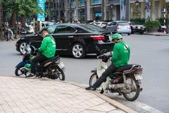 Hanoi, Vietnam - 7 de julio de 2017: Asga al cliente que espera del conductor de la moto para en la calle de Trieu de los vagos V Foto de archivo libre de regalías