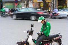 Hanoi, Vietnam - 7 de julio de 2017: Asga al cliente que espera del conductor de la moto para en la calle de Trieu de los vagos V Fotografía de archivo