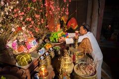 Hanoi, Vietnam - 22 de junio de 2017: Viejo hombre que prepara ofrendas de la adoración en el altar el día de fiesta en casa comu Imágenes de archivo libres de regalías