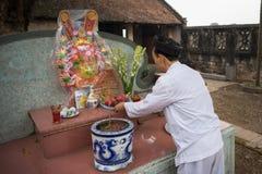 Hanoi, Vietnam - 22 de junio de 2017: Viejo hombre que prepara ofrendas de la adoración en el altar el día de fiesta en casa comu Imagen de archivo libre de regalías