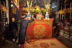 Hanoi, Vietnam - 22 de junio de 2017: Viejo hombre que prepara ofrendas de la adoración en el altar el día de fiesta en casa comu Fotografía de archivo libre de regalías