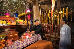Hanoi, Vietnam - 22 de junio de 2017: Viejo hombre que prepara ofrendas de la adoración en el altar el día de fiesta en casa comu Fotografía de archivo