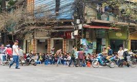 Hanoi, Vietnam - 15 de marzo de 2015: La gente bebe la fruta del café, del té o del jugo en parada del café en la acera en la cal Fotografía de archivo libre de regalías