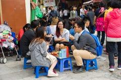 Hanoi, Vietnam - 15 de marzo de 2015: Parada en la calle de Hoan Kiem - la calle más corta del té de Hanoi La gente se sienta en  Imagen de archivo libre de regalías